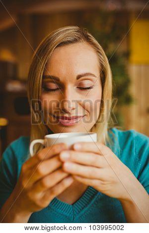 Close-up of young woman holding coffee cup with eyes closed in restaurant
