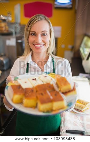 Portrait of happy female worker serving pastries in plate at bakery