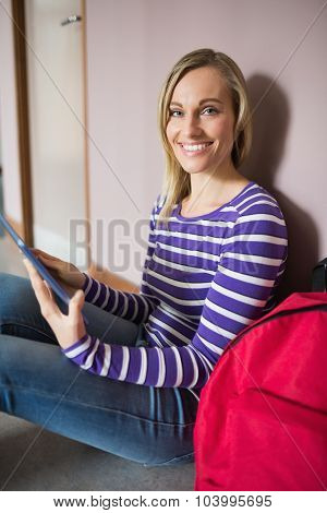 Portrait of female student smiling while using digital tablet in college