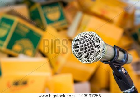 Microphone On A Stand With Blurred Brown Paper Box.