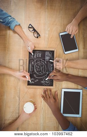 Close-up of cropped hands writing business terms on slate with person touching digital tablet at table