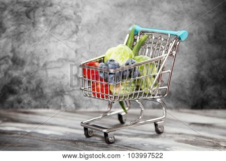 Shopping cart with vegetables on black background.