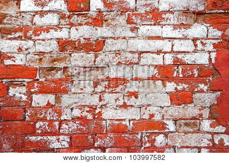 Weathered brick wall half painted in white color