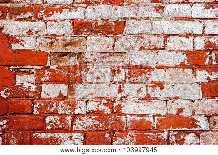 Weathered brick wall with word paint, half painted weathered surface