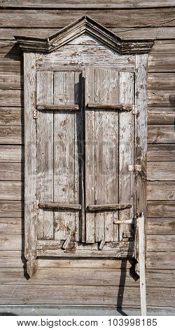 Traditional russian wooden house window with locked shatters in Astrakhan, Russia