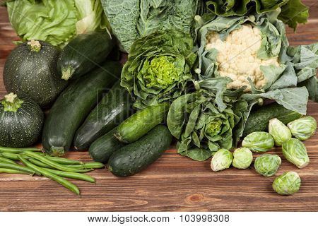 Assortment of green vegetables on wooden surface