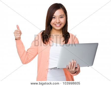 Asian woman use of the notebook computer and thumb up
