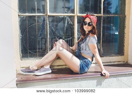 Outdoor bright summer portrait of stylish cheeky young hipster woman sitting at windowsill have long brunette hairs perfect tanned fit slim body wearing denim overall bright bandana