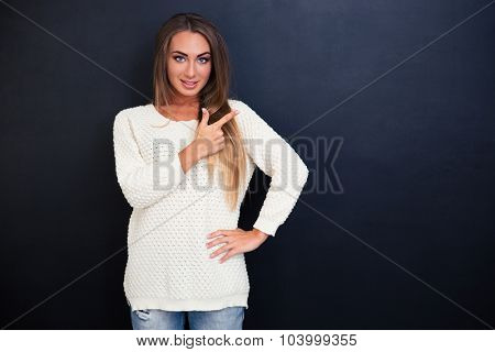 Portrait of a happy young girl pointing finger away over gray background and looking at camera