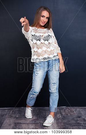 Full length portrait of a happy girl pointing finger at camera on gray background