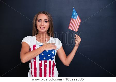 Portrait of a happy patriotic girl holding USA flag on gray background