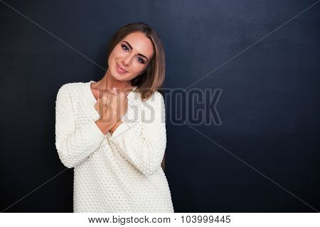 Portrait of a beautiful cute girl looking at camera over gray background