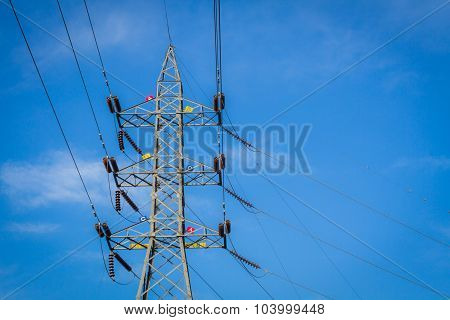 High Voltage Tower With English Alphabet On The Tower, Blue Cloudy Sky Background.
