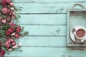 Vintage wooden tray with porcelain teacup and pink flowers on shabby chic mint background, top view  poster