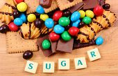 Постер, плакат: A Lot Of Sweets With Word Sugar On Wooden Surface Unhealthy Food