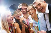 stock photo of christmas song  - Photo of businesspeople with flutes of sparkling champagne singing Christmas songs - JPG