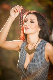 foto of grape  - Beautiful woman in gray posing in autumnal park holding a ripe grapes bunch - JPG