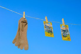 foto of clotheslines  - Odd socks and bank note hanging on a clothesline on a sky background - JPG