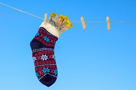 image of clotheslines  - Odd socks and bank note hanging on a clothesline on a sky background - JPG