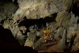 picture of plinth  - Daylight pours in through a large crack in the mountain to illuminate this golden buddha - JPG