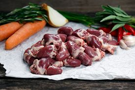 foto of giblets  - Raw Duck hearts on crumpled paper decorated with greens and vegetables - JPG