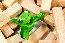 pic of creatures  - Green plasticine creature looking up standing on a block of wood - JPG