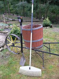 image of spade  - Spade and rake leaning against an old wheelbarrow in the garden  - JPG