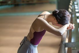 foto of ballet barre  - The weary classic ballet dancer at ballet barre on a rehearsal room background - JPG