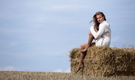pic of haystacks  - Full length portrait of young adult girl on haystack against blue sky with clouds and autumn field wear white sweater - JPG