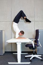 foto of scorpion  - flexible business man in scorpion asana on desk in his office  - JPG