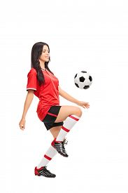 foto of juggling  - Full length profile shot of a female soccer player juggling a ball on her knee isolated on white background - JPG