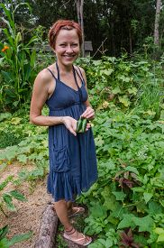 foto of jalapeno  - Smiling young woman showing two jalapeno peppers she just picked from her garden - JPG