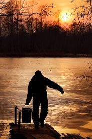stock photo of water shortage  - A man is collecting water from a pond in spring - JPG