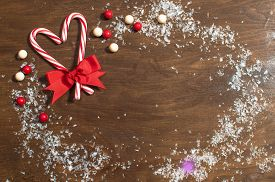 picture of gumballs  - Two Christmas candy cane in heart shape and snow frame with gumballs on wooden background - JPG