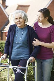 picture of zimmer frame  - Daughter Helping Senior Mother To Use Walking Frame - JPG
