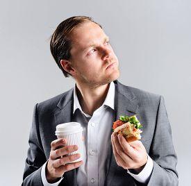 foto of takeaway  - Busy businessman eating takeaway sandwich on the go - JPG
