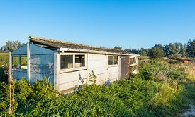 pic of slab  - Old dilapidated small shed made of concrete slabs and with a corrugated roof in early morning sunlight in the fall season - JPG