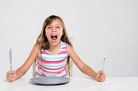 foto of table manners  - Hungry angry young girl screaming - JPG