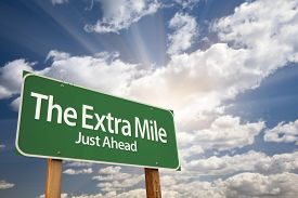 pic of mile  - The Extra Mile Green Road Sign With Dramatic Clouds and Sky - JPG