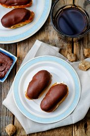 pic of eclairs  - eclairs with cheese cream and chocolate glaze on a dark wood background - JPG