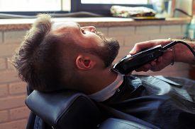 image of barber razor  - barber shaving beard with electric razor in barber shop - JPG