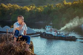 stock photo of barge  - Pensive man sitting on the cliff above the river at sunset looking at barge with sand passing by  - JPG