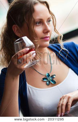 Beautiful woman drinking cognac.