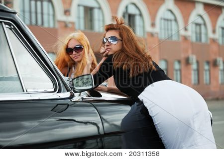 Two young women with retro car on a city street.