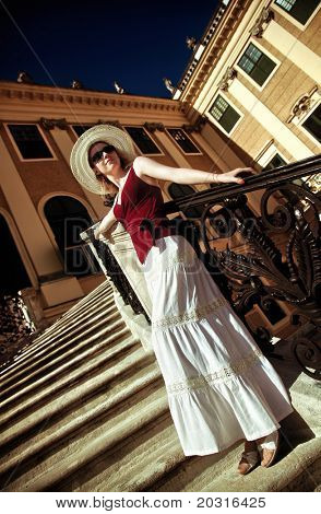 Young elegant woman on stairs. Camera angle view.