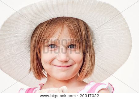 A girl of six years in a hat, his hair disheveled