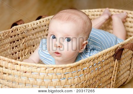 Surprised baby Lying In Wicker Basket