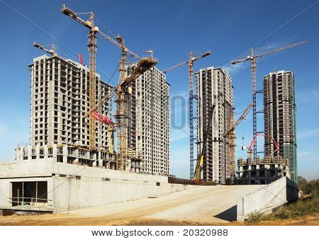 Four tall buildings under construction with cranes against a blue sky