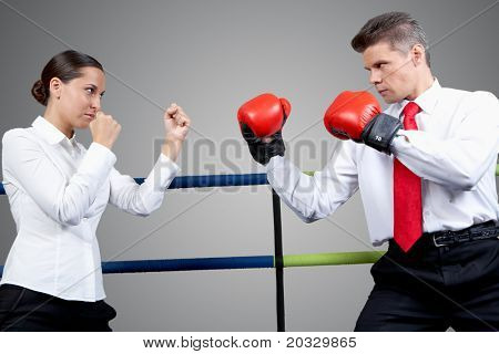 Portrait of aggressive businessman in boxing gloves and serious female in conflict with each other