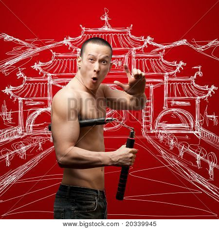 funny muscular shaolin monk with nunchaku in his hands